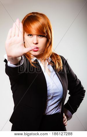 Redhair businesswoman with stop hand sign gesture on gray. Business concept. Studio shot.