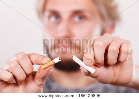 Young Man Is Breaking A Cigarette