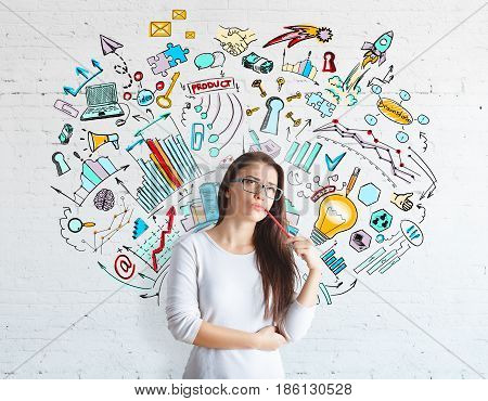 Portrait of attractive thoughtful young european woman on brick background with business sketch. Entrepreneurship concept