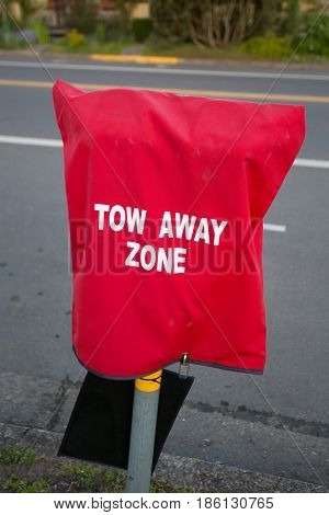 Red hood over a parking meter with tow away zone printed on in preparation for the Eugene Marathon.