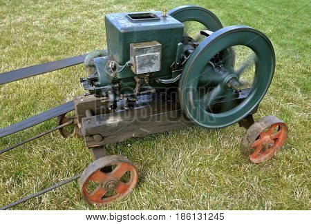 An old restored gas engine with a heavy fly wheel on a portable cart is belted and operating. poster