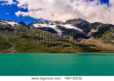Lago Bianco and the mountains of the Bernina range at the Ospizio Bernina under white clouds in summer. This is the highest point on the Bernina Railwayline. Poschiavo Engadin Grisons Switzerland