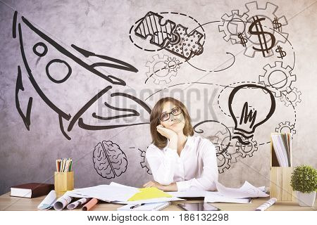 Thoughtful young woman daydreaming at workplace with creative rocket sketch. Start up concept