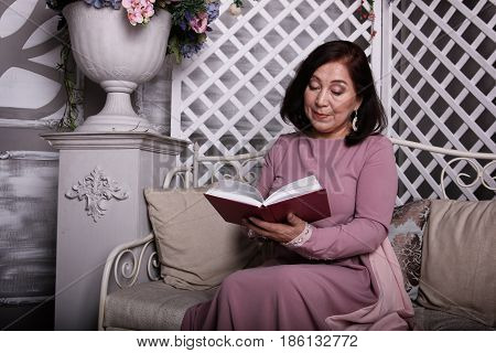 Mature well-dressed asian woman reading a book at home.