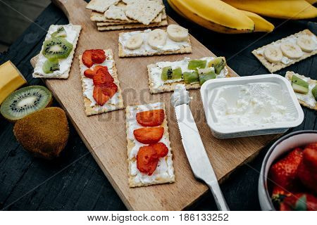 Light Snack Of Water Cracker Sandwiches With Cream Cheese And Fruits: Bananas, Strawberries And Kiwi