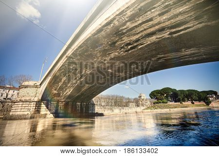 Garibaldi bridge in Rome, Italy. Tevere river. Ancient Roman bridge seen from below, on the quay of the river Tiber in Rome, Italy. Blue sky. Tiber Island on the right.