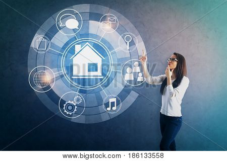 Attractive young woman pointing at circular futuristic interface of smart home automation assistant on concrete background. 3D Rendering