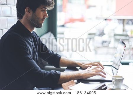 Editor of popular online magazine typing text of new book review uploading it on web site making skrip inspiring  literature using laptop conmputer  wifi connection