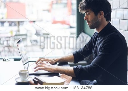 Typing text of new book review uploading it on web site after making skrip inspiring by literature using laptop computer and wifi connection