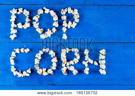 Word popcorn written with pop corns above blue wooden background flat lay.