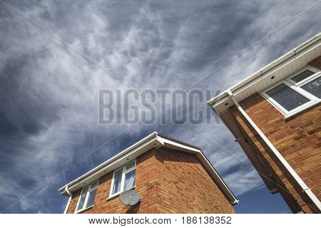 British Detached House made of Red Brick Against Blue Cloudy Sky