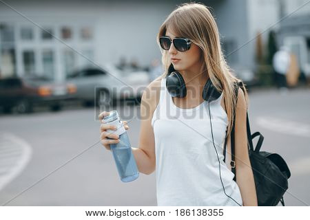 beautiful girl with big black headphones drinking water from bottle