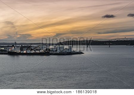 Auckland New Zealand - March 6 2017: Westhaven oil terminal with docked tanker at sunset. Orange sky Silver water. Auckland Harbour Bridge in photo.
