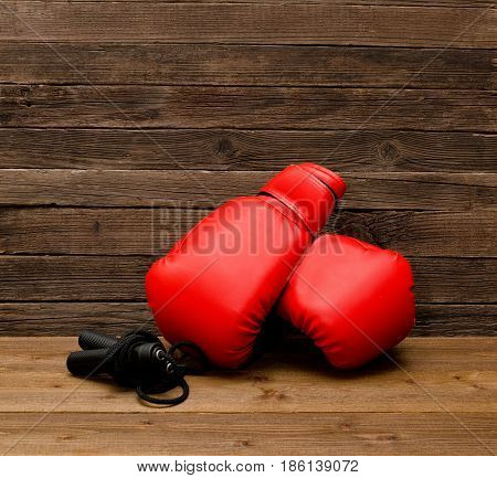 Two Red Boxing Gloves Lie On A Wooden Brown Background, Skipping Rope Empty Space