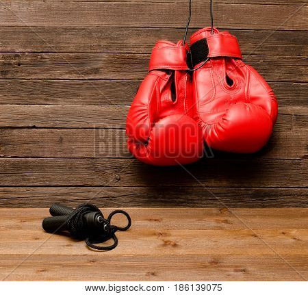 Two Red Boxing Gloves Hung On A Wooden Brown Background, Jump Rope