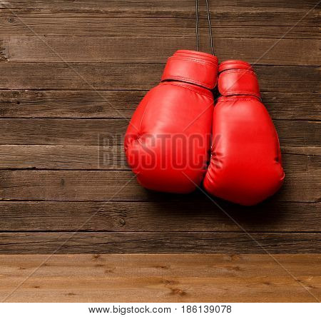 Two Red Boxing Gloves Hung On A Wooden Brown Background, Empty Space