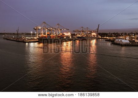Auckland New Zealand - March 6 2017: The container terminal in late evening with ships. Lights on the docks reflected in the water.