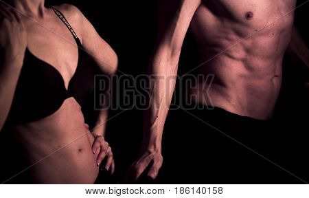 Sexy couple semi nude slim athletic man and erotic slender lady naked touching bodies in underwear in dark.