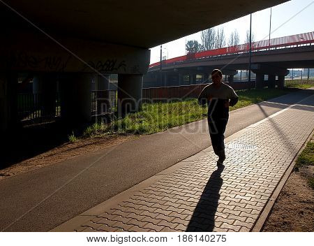 Morning run Lodz, Poland - May 12, 2017 The man under the railway viaduct, cultivates morning recreation running in Lodz.