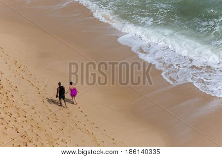 PRAIA DA MARINHA, PORTUGAL - APRIL 24, 2017: People at the famous beach of Praia da Marinha in Lagoa. This beach is a part of famous tourist region of Algarve.