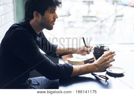 Writing in notebook about his traveling adventures in blog while sitting in cozy coffee shop interior, professional journalist creating new article about art of photography