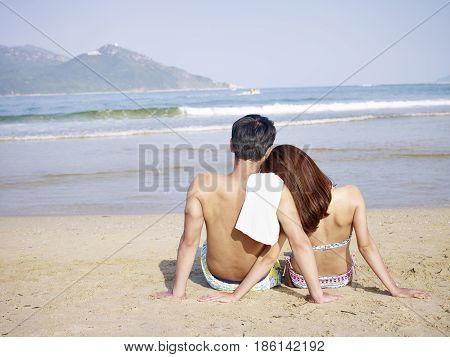 young asian couple lovers sitting on beach rear view.