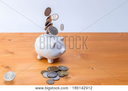 White Moneybox Piggy Safe Bank With Coins In The Front And Falling From The Top Isolated On White Ba