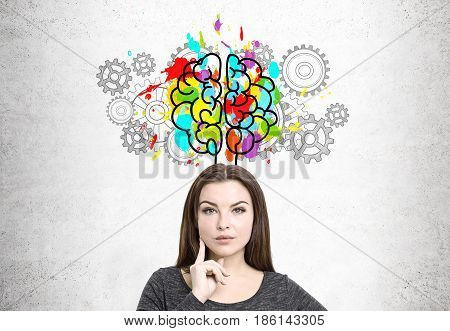 Close up of a pensive young woman with brown hair. She is standing near a concrete wall with a colorful brain sketch surrounded with gears.