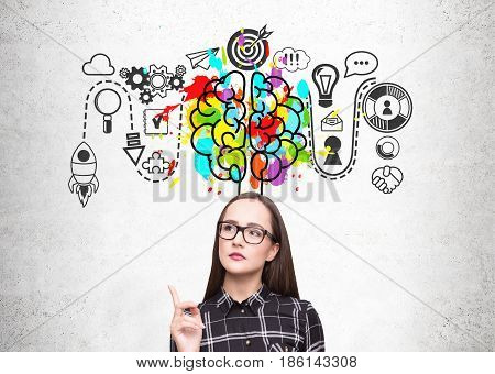 Close up of a nerdy girl wearing a checkered shirt and glasses. She is standing near a concrete wall with a start up sketch and a colorful brain icon