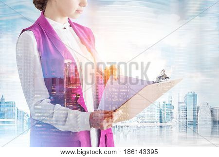 Portrait of an unrecognizable woman in white and pink clothes holding a clipboard and standing against a city panorama. Toned image double exposure
