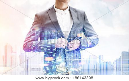 Close up of an unrecognizable businessman buttoning his suit standing against a city panorama. Mock up toned image double exposure
