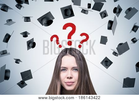 Close up of a young woman s head with brown hair. She is standing near a gray wall with graduation hats and three question marks above her head