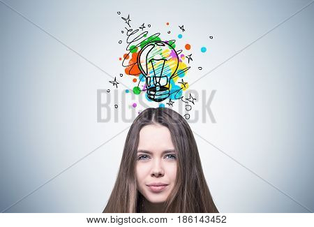 Close up of a young woman s head with brown hair. She is standing near a gray wall with a small colorful light bulb above her head
