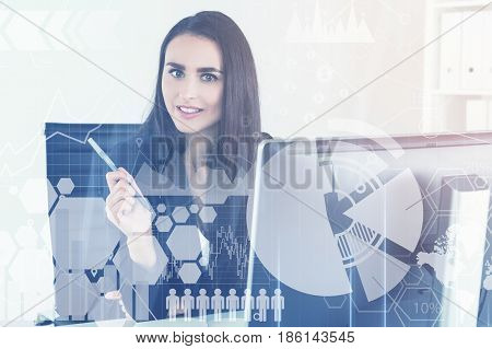 Portrait of a motivated successful businesswoman looking at the viewer while sitting at her workplace in an office. Graphs in the foreground. Toned image