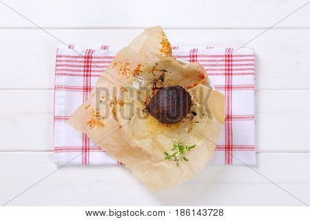 baked whole beet with olive oil and thyme on baking paper and checkered dishtowel
