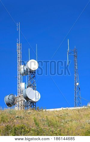 Communication towers against blue sky