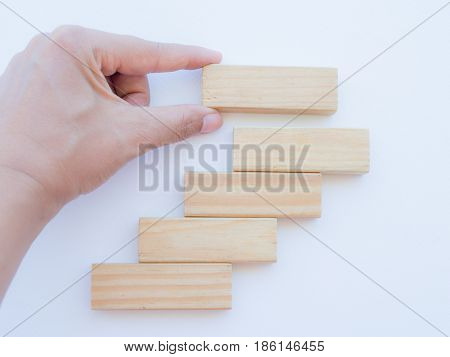 Concept of building success foundation. Women hand put wooden blocks in the shape of a staircase
