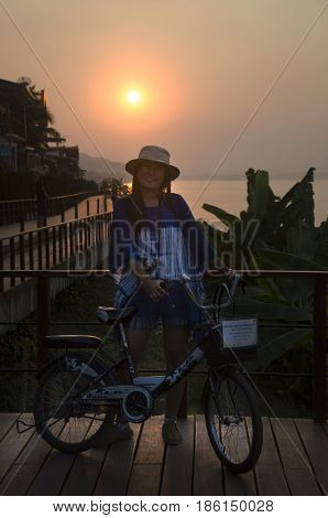 Asian Thai Woman Posing With Bicycle And Travelers People Walking Relax At Riverside Mekong River In