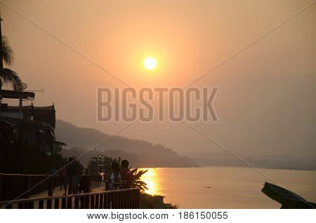 Travelers People Take Photo At Riverside Of Mae Khong River With Reflection Of Sun In Sunset Time At