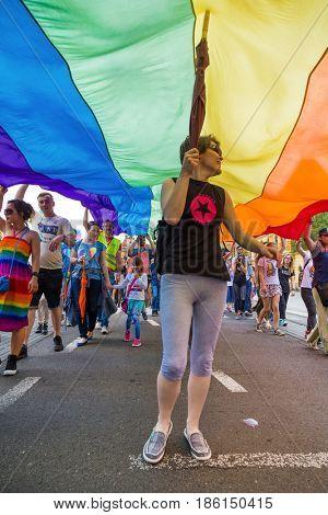 ZAGREB, CROATIA - JUNE 11, 2016: 15th Zagreb pride. LGBTIQ activist under big rainbow flag.