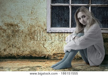 The girl sits on the floor by the window in the old room it's raining outside.