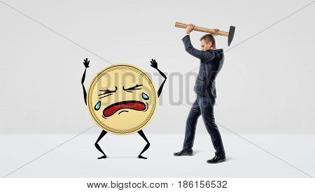 A businessman holding a large hammer over a golden coin with arms, legs and a crying face. Credit and loss. Business expenses. Loss of profit.