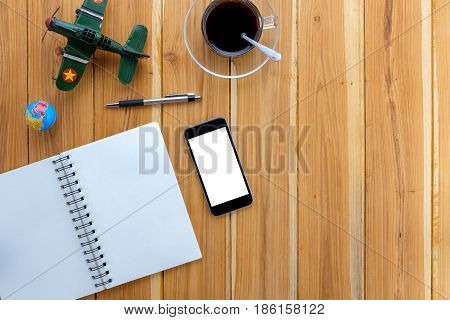 Office desk with blank screen smartphonepennotebook and coffee cup on wood table.Top view with copy space.Office supplies and gadgets on desk table.Working desk table concept.Flat lay image.