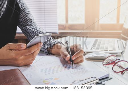 Business woman working with smart phone and discussing the analysis charts or graphs on modern White office desk table .Business concept.