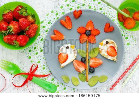 Food art idea for kids - lovebirds pancakes on strawberry kiwi blueberry flower