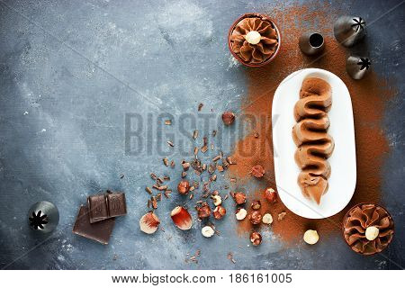 Delicious chocolate mousse with nuts on a dark table with ingredients top view