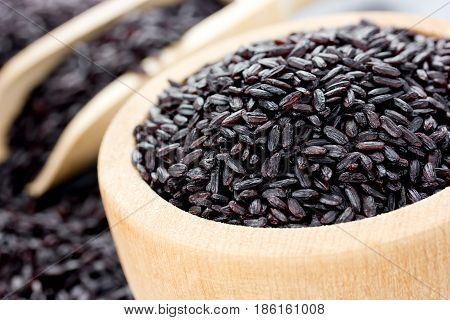 Unpolished black rice in a wooden bowl closeup poster