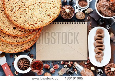 Preparation of chocolate cake from biscuit cakes with chocolate cream with empty space in craft cookbook to write recipe