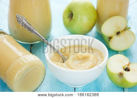 Green apple puree with fresh apples and apple puree in jars on the table