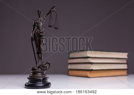 The goddess of justice on a white table against the background of the books.